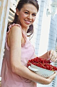 Young woman with fresh red currants