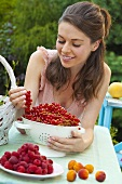 Young woman admiring a bunch of red currants