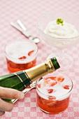 Champagner mit Erdbeeren eingießen