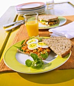 Open faced sandwich with grated carrot, mustard and egg