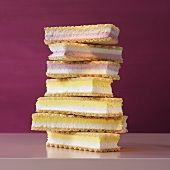 A stack of cream-filled wafers in front of a rose colored background