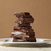Melted pieces of chocolate stacked in front of a light brown background