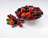 Assorted berries in a glass dish with more berries next to it