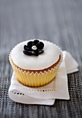 Cupcake with white icing and black candy flower