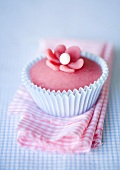 Pink muffin on a checked towel