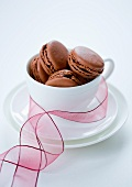 Chocolate macaroons in a teacup with ribbon