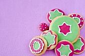 Bunt verzierte Weihnachtsplätzchen auf lila Hintergrund