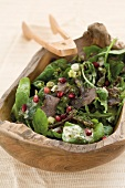 A green salad with biltong and pomegranate seeds