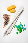 Ingredients for cake pops (sugar beads, sticks, coloured sugar strands and icing drops)