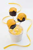 Cake pops shaped like chocolate marshmallows with yellow icing in a cup of yellow sugar beads