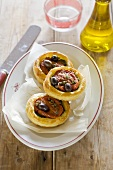 Puff pastry tartlets with tomatoes, courgette and olives