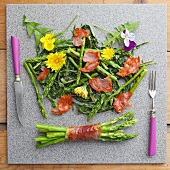 Roasted green asparagus with parma ham and edible flowers