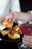 A Cosmopolitan and fried won ton sheets topped with avocado and trout caviar
