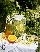 Elderflower syrup and orange syrup on a garden table