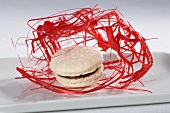 A white chocolate macaroon with red sugar threads