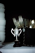 A mini trophy, cutlery and crockery on a buffet table