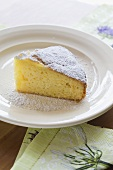 A slice of olive oil cake with icing sugar