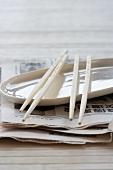 Teller und Essstäbchen auf asiatischer Zeitung