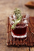 A sprig on rosemary on a glass of red wine