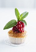A muffin topped with redcurrants and mint
