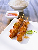 Chicken satay kebabs with a sweet and sour sauce and rice