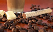 A chocolate latte, a macchiato stick and coffee beans