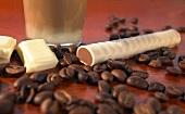 A chocolate latte, a macchiato stick and coffee beans