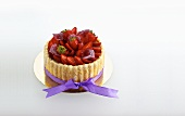 A mini strawberry tart with a purple bow