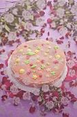 A cake with pink sugar icing and flowers underneath a veil