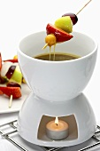 A butterscotch fondue with fruit kebabs