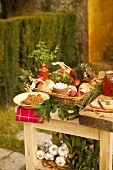 A garden table laid with vegetables, bread, spreads, herbs and honey