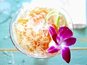 A cocktail garnished with an orchid