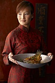 A woman serving wok-fried carp (China)
