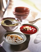 Three desserts in bowls with oriental spoons