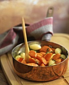 A carrot and onion medley in a copper pot