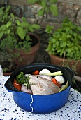 A raw chicken in a pot with ingredients for poaching
