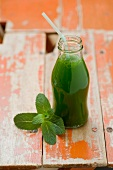 A cucumber smoothie in a bottle with a straw