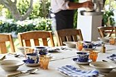 A table laid outside with a blue and white cups