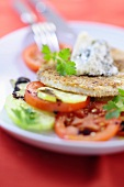 Celery escalope with a nut crust and gorgonzola cream on tomatoes