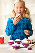 A blonde girl eating a muffin