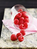 Fresh raspberries spilling out of a glass