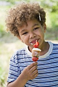 A little boy eating a strawberry muffin kebab