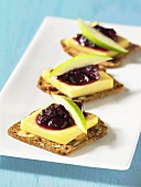 Crackers topped with cheese, blueberry chutney and apple wedges