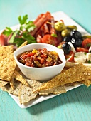 An antipasti platter with bread and tomato salsa