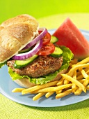 A turkey burger with chips and watermelon