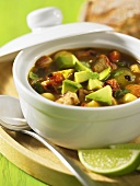 Chicken soup with avocado in a pot with lime wedges