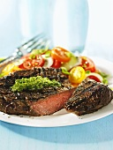 A grilled bison steak with herb sauce and tomato salad