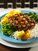A pork chop with a pineapple glaze, rice and pineapple pieces