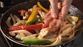 Cooking vegetables and chicken breast fillet in frying pan
