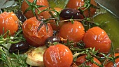 Frying tomatoes, olives and herbs
